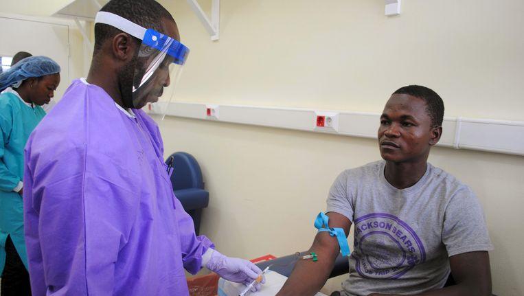 Een hulpverlener prikt bloed van een overlevende in Monrovia. (archieffoto)