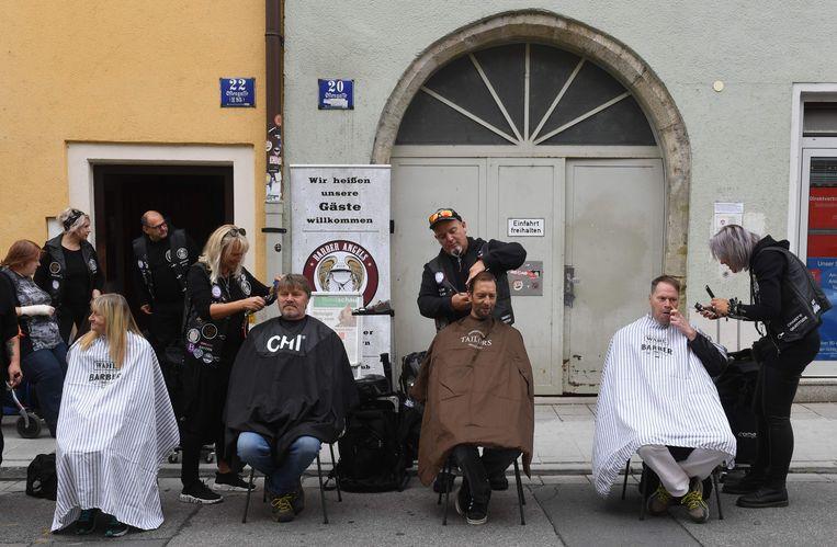 In de Zuid-Duitse stad Regensburg worden daklozen door de Barber Angels Brotherhood onder handen genomen – kappers met een leren jas die goeddoen. De barberbende is actief in meerdere landen.  Beeld AFP