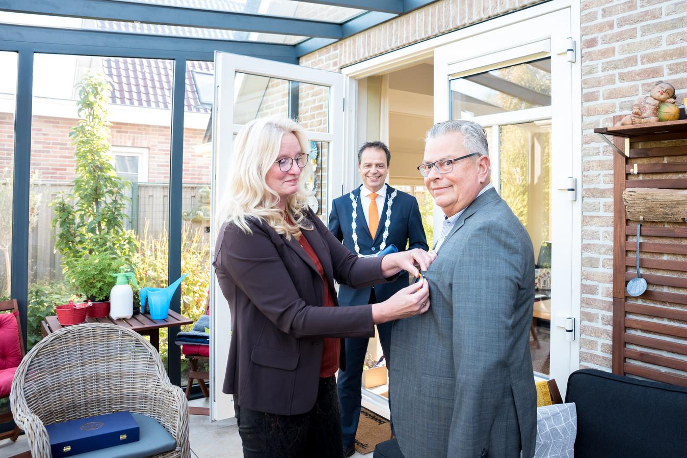 Ferry van Dorst krijgt van partner Leonieke Goutier het lintje opgespeld dat hoort bij zijn koninklijke onderscheiding als Ridder in de Orde van Oranje-Nassau. Burgemeester Jack van der Hoek kijkt op de achtergrond toe.