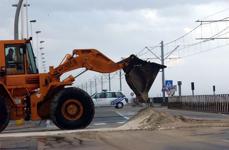 Een kraan verwijdert het opgewaaide zand langs de Zeedijk in Raversijde.