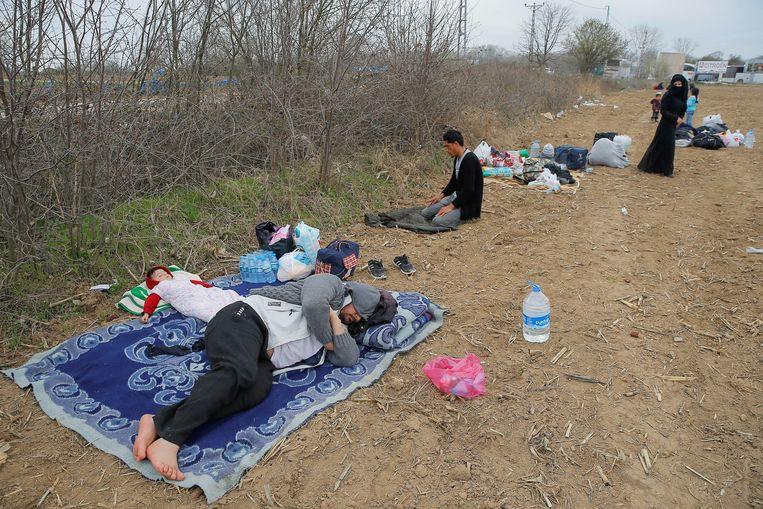 Migranten rusten uit in de buurt van de landsgrens tussen Turkije en Noord-Griekenland. Beeld REUTERS