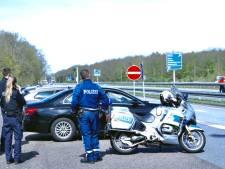 Duitse politie controleert bij de grens en waarschuwt met bord: 'Bleiben Sie bitte zu Hause!'