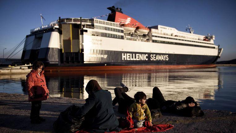 Vluchtelingen op het eiland Lesbos wachten voor een Griekse veerpont. Die moet de vluchtelingen naar Athene brengen. Beeld Afp