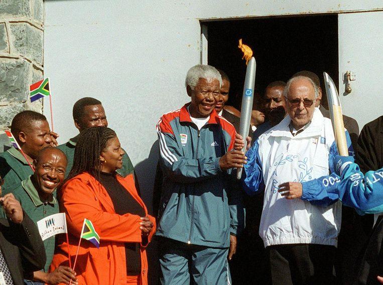 Mandela en Kathrada houden het olympisch vuur samen vast bij de ingang van gevangenis Robbeneiland. Beeld afp