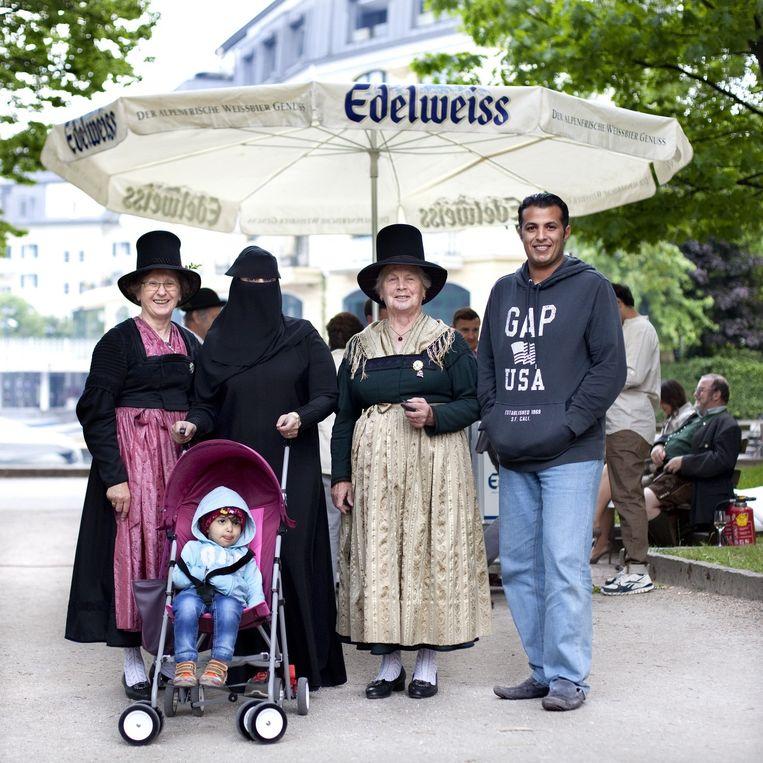 Gevarieerd zomers straatbeeld in Zell am See: Boerka en traditionele Oostenrijkse klederdracht samen op één foto.