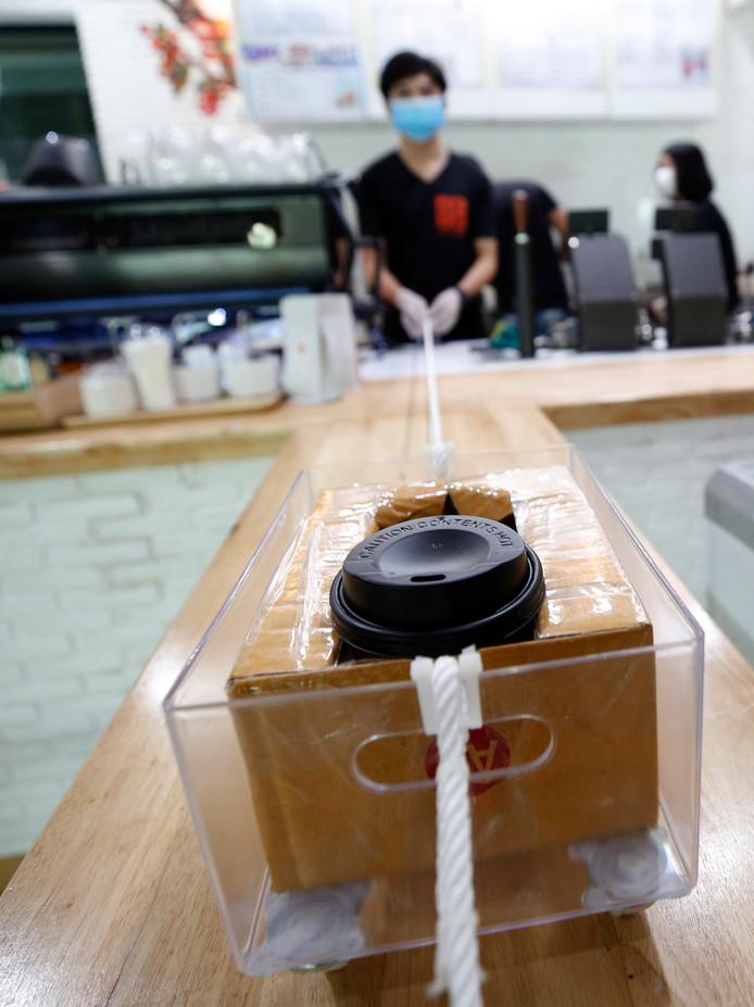 In koffiebar Art of Coffee in Bangkok is het afstand houden heilig. Medewerkers hebben een ingenieus systeem bedacht om klanten te kunnen voorzien van hun kop koffie. Die wordt in een plastic bakje op wieltjes, bevestigd aan een koord, naar de klant gebracht.