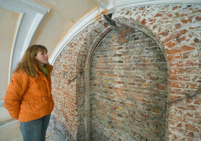 Barbara van Dijk bij het raam dat ontdekt is bij de renovatie van de voormalige kerk. foto Willem Mieras