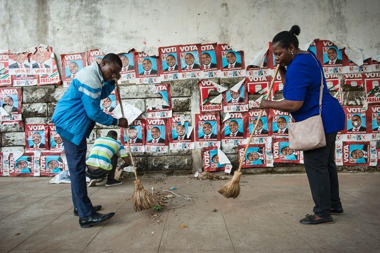 Leden van een kerk vegen een van Maputo's straten tegen de achtergrond van een muur vol met posters van regeringspartij Frelimo. Beeld Bram Lammers
