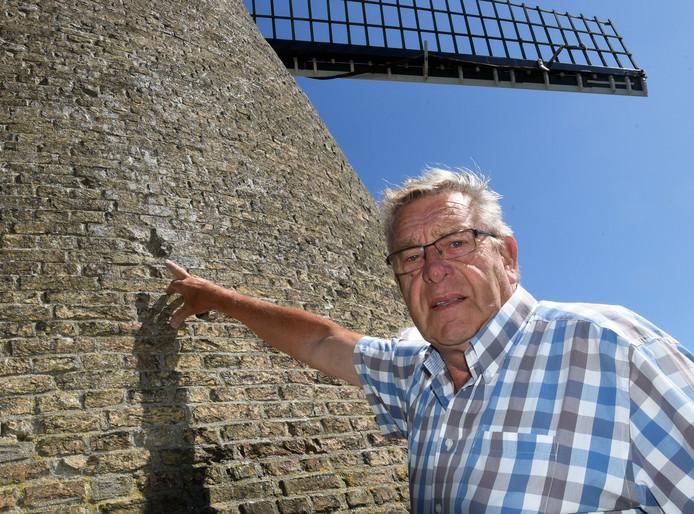 Sjaak Michielsen, voorzitter Stichting Molen Nieuwvliet, wijst kapotte steen aan in de molen van Nieuwvliet die herinnert aan granaataanvallen bij de bevrijding van Nieuwvliet eind oktober 1944.