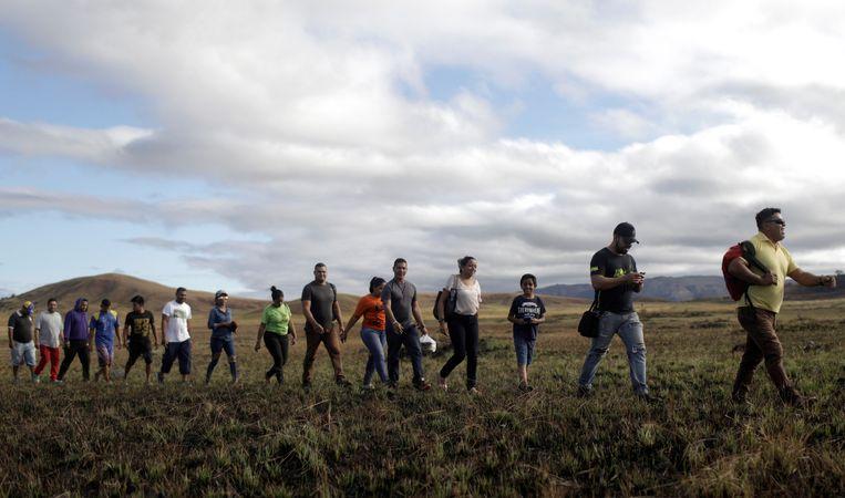 Mensen steken de grens over tussen Venezuela en Brazilië.