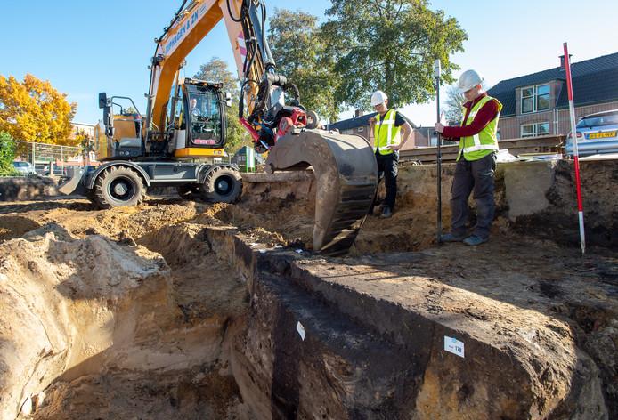 Timo Vanderhoeven (blote armen) en Lars Schaarman (rood shirt) doen archeologisch onderzoek in Epe. De donkere verkleuring in de grond, duidt op een waterput die hier in het verleden heeft gezeten.