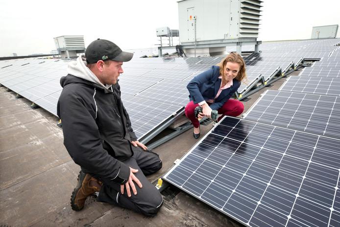 Wethouder Greetje Bos - op een foto uit begin 2019 - waar ze  symbolisch het laatste zonnepaneel vastschroeft op het dak van de evenementenhal op Breepark.