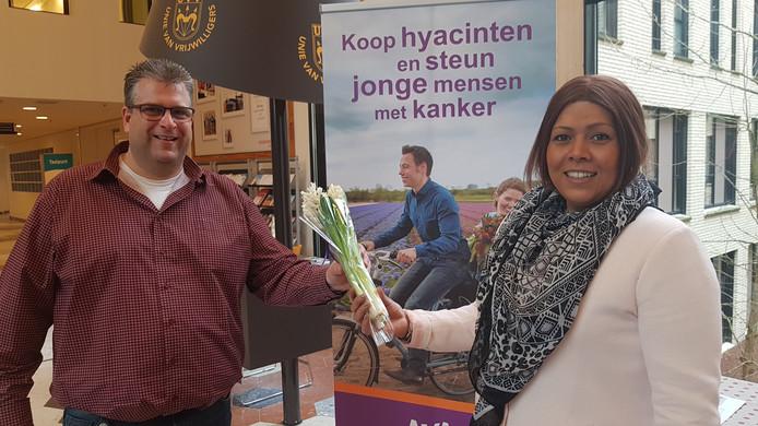 Vrijwilligster Sabrina Kotta krijgt één van de laatste bosjes van teamleider logistiek Léon Koolen van het JBZ.