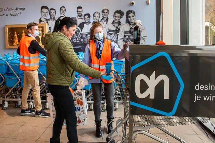 Anne Karremans, normaal afwashulp in een restaurant, is vandaag gastvrouw in de Albert Heijn in Made. Supermarktmanager Twan van Meel (links) helpt de horeca door tijdelijk hun personeel in dienst te nemen.