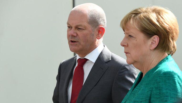 Scholz en Angela Merkel spreken met de politie na de rellen op de G20 in Hamburg. Nu zullen zij samen werken in de GroKo. Beeld reuters