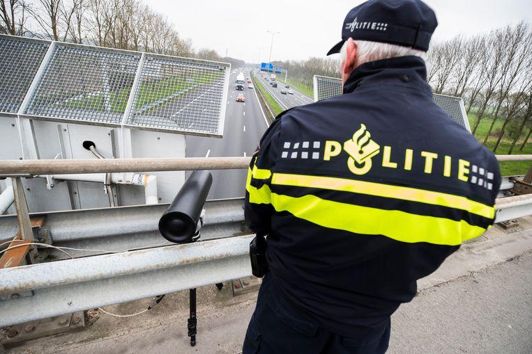 Een politieagent bij een flitscamera op de snelweg.  Beeld ANP