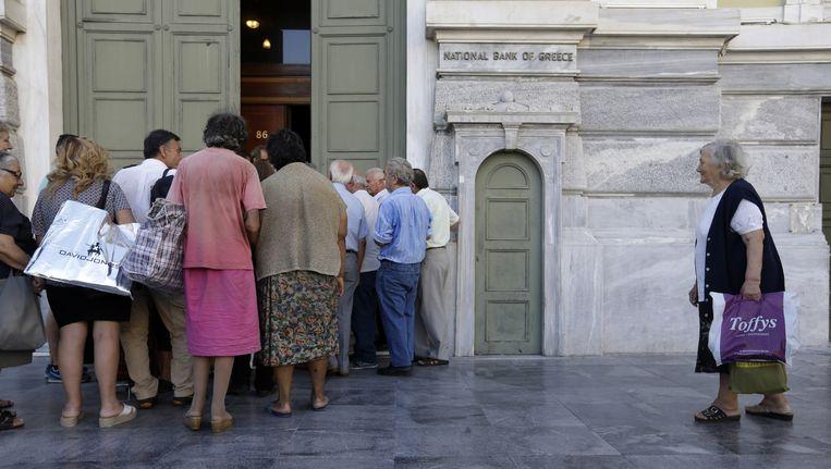 Grieken wachten geduldig aan het hoofdkantoor van de Nationale Bank van Griekenland.