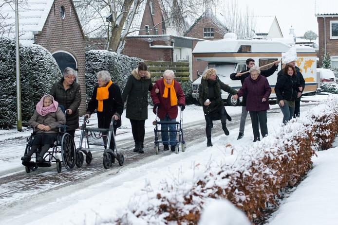 Bewoners en begeleiders van Brugstede in Lemelerveld trotseren de kou en en sneeuw op maandag 11 december.