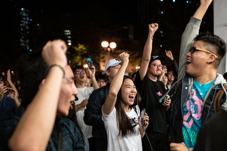 Aanhangers van het pro-democratiekamp juichen wanneer een pro-Peking-kandidaat zijn zetel verliest.