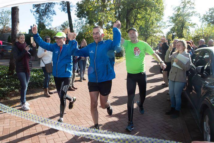 Dankzij zijn atletiekvrienden kon de slechtziende Ludo Hoendervangers (midden) uit Putte zaterdag toch een hele marathon door de gemeente Woensdrecht lopen, met start en finish bij hem thuis voor de deur.