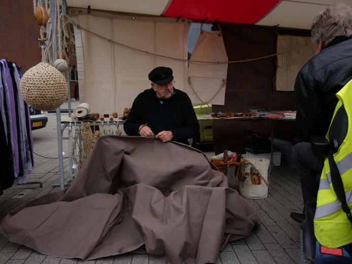 Een zeilmaker aan het oude handwerk. (archieffoto)
