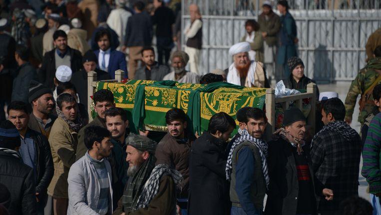 Rouwenden in Afghanistan dragen de kist met een van de slachtoffers van de aanslag op hulpverleners van het Internationale Rode Kruis, woensdag in de noordwestelijk provincie Jowzjan. Er kwamen zes hulpverleners om, twee anderen zijn nog vermist. Beeld AFP
