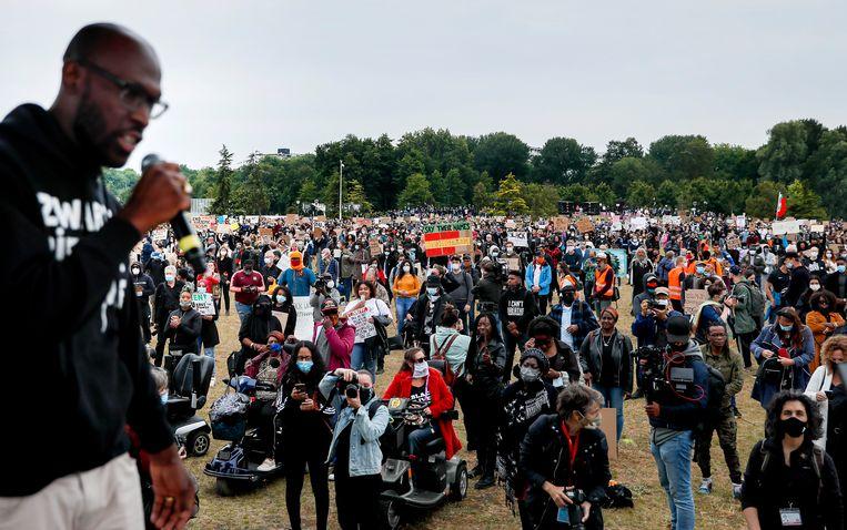 Demonstranten tijdens een demonstratie tegen racisme in het Nelson Mandelapark in de Bijlmer. Vooraan met microfoon: Mitchell Esajas. Beeld ANP/ Remko de Waal