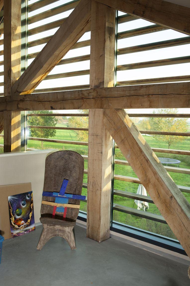 Vanuit haar atelier heeft Lisette uitzicht over het Aadal. Een zijtak van het riviertje de Aa staat in verbinding met de molen. Het houten stoeltje komt uit het Afrikamuseum in Berg en Dal. Beeld Jaap Scheeren