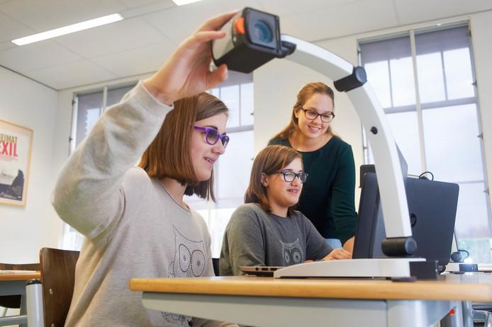 De tweeling Amber (voor) en Fleur met op de achtergrond leerlingbegeleider Janine van Oss.