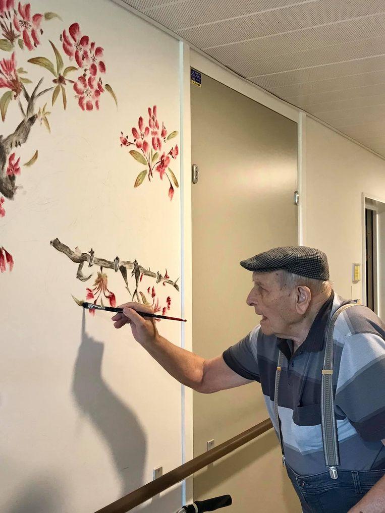 Op sociale media wordt deze foto van een schilderende 95-jarige Maurice Dhoop uit Kuurne gretig gedeeld. Hij toont even wat hij in zijn mars heeft, alvorens Melissa Bertolino het penseel opnieuw overneemt.