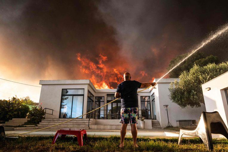 Een man houdt zijn woning nat in La Couronne, nabij Marseille. Beeld AFP