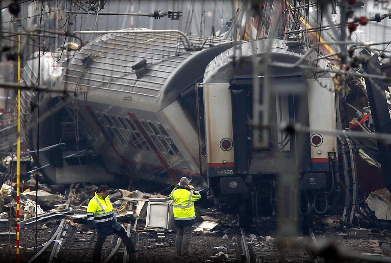 Medewerkers van de Belgische spoorwegen kijken naar de wrakstukken van een van de treinen.