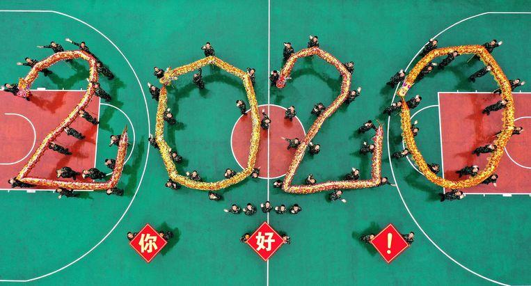 Chinese agenten in Shenzen voeren een drakendans uit waarbij ze het getal 2020 vormen.  Beeld AFP