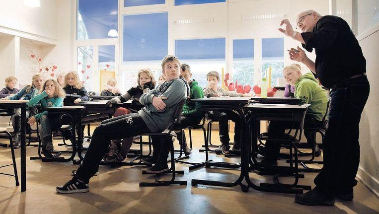 Meester Gerard Weinans tijdens de les aan groep 6, 7 en 8 van de Heilig Hartschool in het Groningse Mussel. Beeld Reyer Boxem