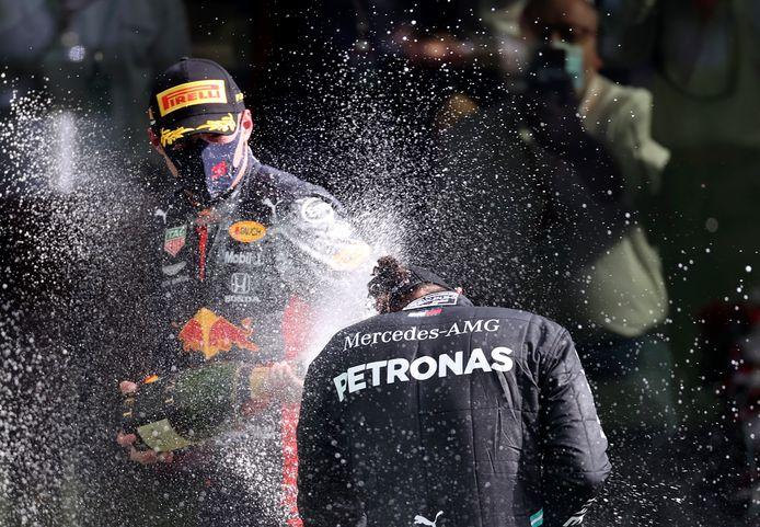 Max Verstappen spuit Lewis Hamilton nat met champagne na de GP van België, afgelopen weekeinde.
