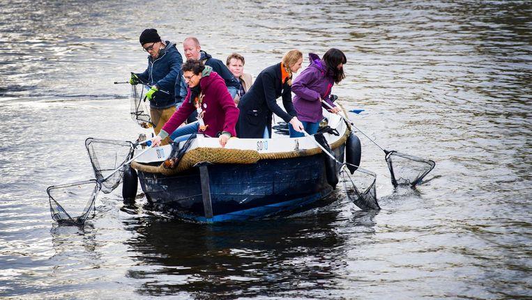 Jongeren vissen met schepnetten afval uit de Amsterdamse grachten om zo bij te dragen aan een beter milieu. Beeld anp