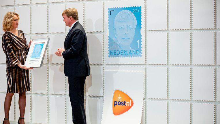 Koning Willem-Alexander ontvangt van Herna Verhagen, bestuursvoorzitter van PostNL, het eerste exemplaar van de nieuwe permanente koningspostzegel van PostNL. Beeld anp
