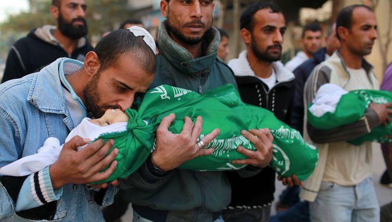 Een vader kust zijn twee kinderen op hun begrafenis zondag. Zijn dochter van 18 maanden en zijn zoon van 3 zijn bij de aanvallen op Gaza om het leven gekomen. Beeld REUTERS