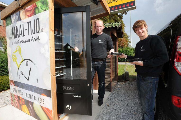 Zaakvoerder André Claessens en Bran Petit vullen de maaltijdautomaten samen aan.
