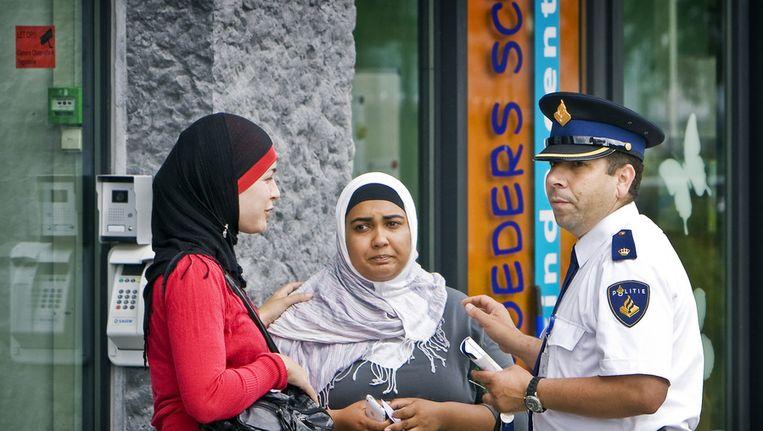 Een politieagent troost een vrouw bij het kinderdagverblijf Moeders Schoot in Amsterdam. Beeld ANP