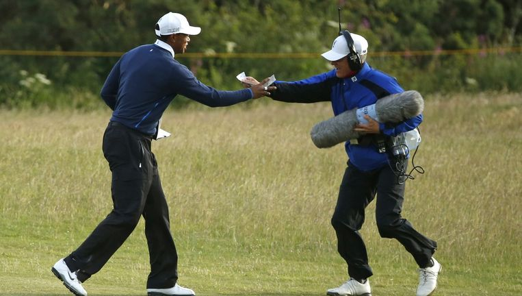 Een geluidsman geeft Tiger Woods zijn scorekaart terug op St Andrews. Die was weggewaaid in de harde wind. Beeld AP