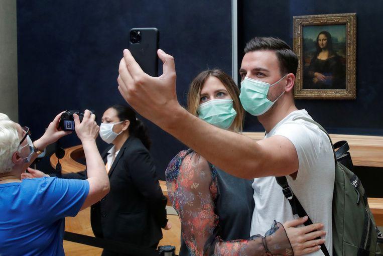 Bezoekers van het Louvre in Parijs dragen mondkapjes terwijl ze een selfie maken voor de Mona Lisa. Beeld REUTERS