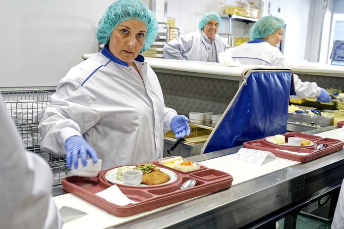 Het portioneren van maaltijden in de bestaande keuken van het JBZ.
