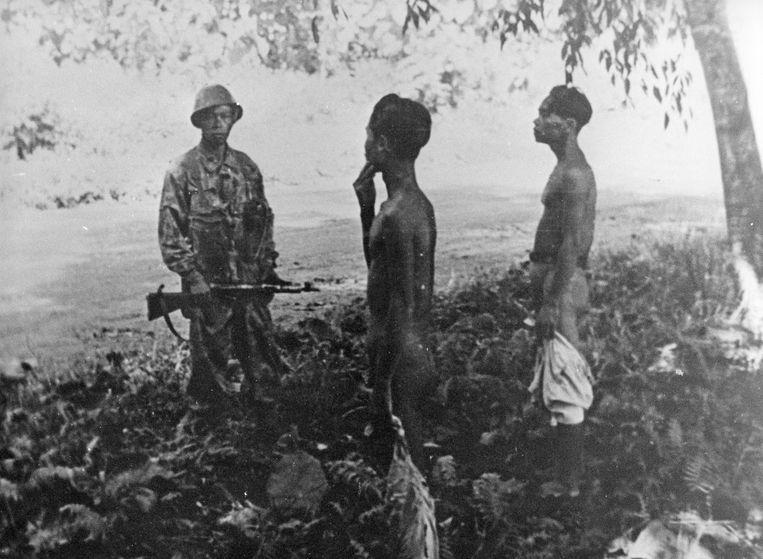 Een KNIL-soldaat bewaakt twee gevangen die verhoord worden tijdens de 'politionele acties' in Indonesië. Beeld