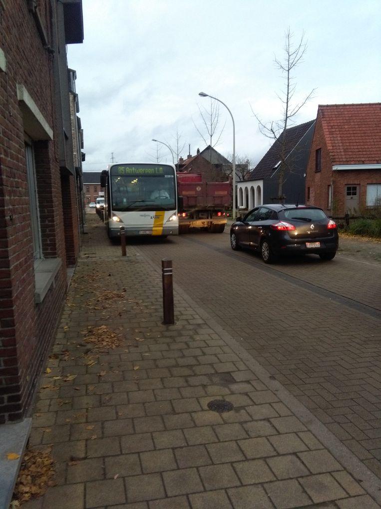 Een bus en vrachtwagen kunnen elkaar niet kruisen zonder uit te wijken op het voetpad.
