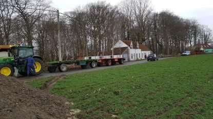 Elektriciteitspaal belandt dwars over de weg na aanrijding door tractor, auto krijgt elektriciteitskabels over zich