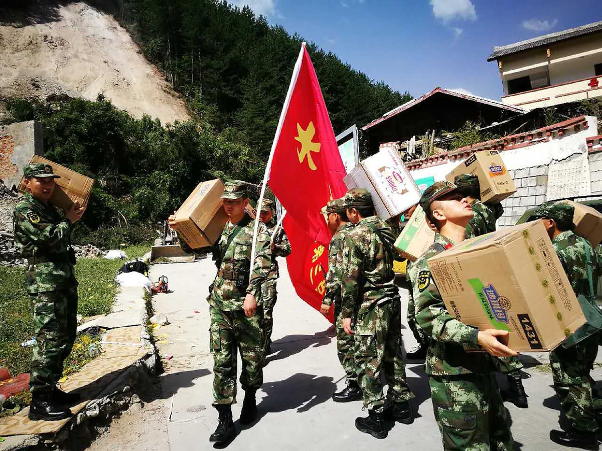 Chinese militairen brengen hulpgoederen naar de getroffen gebieden.