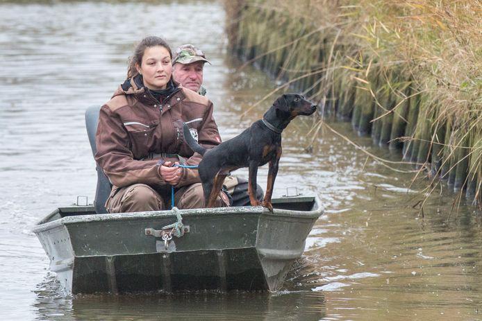 Hunter speurt de waterkant af.  In de boot: Michelle Willems en Stefan Leloux.