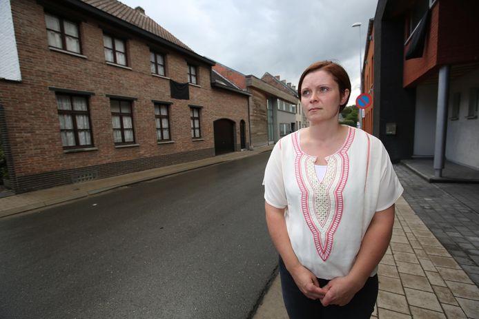 Tine De Mey in de Sint-Jobstraat. Aan de woning van haar ouders (links) hangt de zwarte vlag uit, net zoals bij de overburen.