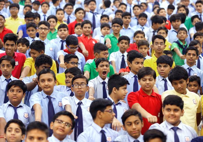 Een schooljongen in Ahmedabad geeuwt terwijl hij en andere leerlingen de eed op een corruptievrij India moeten afleggen. Foto: Amit Dave